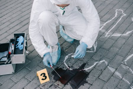 male criminologist in protective suit and latex gloves taking a blood sample at crime scene