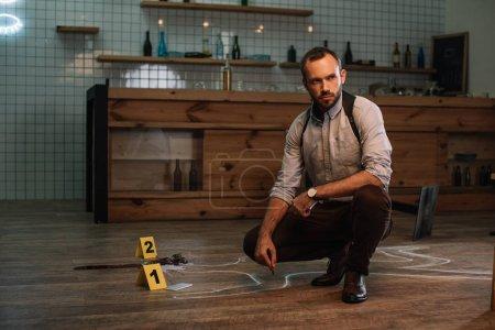 pensive male detective sitting at crime scene