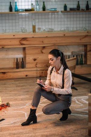 Photo pour Femme détective assis et prendre des notes sur une scène de crime - image libre de droit