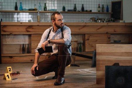Photo pour Détective masculin sérieux assis sur la scène de crime avec un carnet - image libre de droit
