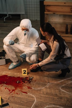 forensic investigator and concentarted female detective taking notes and investigating crime scene together