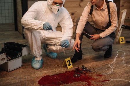 cropped view of forensic investigator and female detective taking notes and examining crime scene