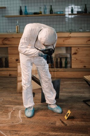 forensic investigator documenting evidence with camera at crime scene