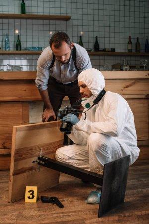 Foto de Investigador forense mostrando picutes en cámara a hombre detective en la escena del crimen - Imagen libre de derechos