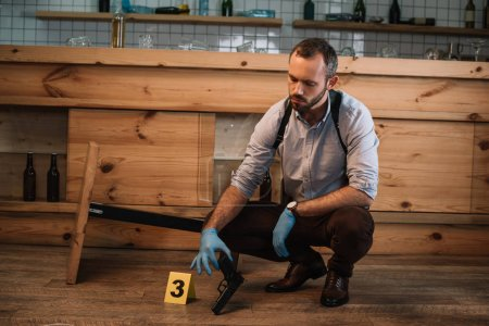 Photo for Serious male detective collecting evidence gun at crime scene - Royalty Free Image