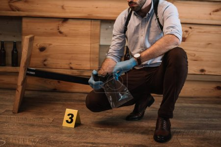 cropped view of male detective collecting evidence gun at crime scene