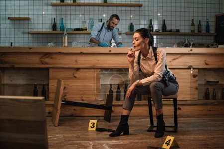 cropped view of smoking female detective sitting at crime scene with colleague working behind