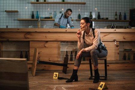 recadrée vue du tabagisme féminin détective assis au lieu du crime avec une collègue de travail derrière