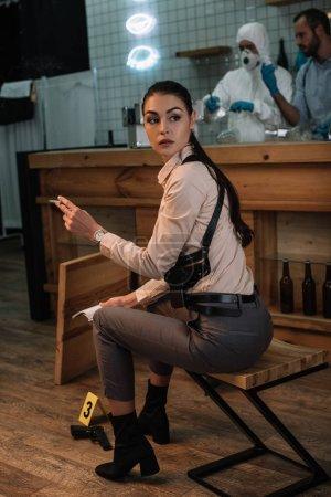 Photo pour Recadrée vue du tabagisme féminin détective assis devant la scène du crime avec des collègues de travail derrière - image libre de droit