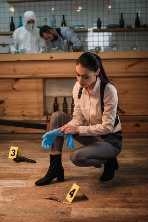 female detective collecting evidence at crime scene with colleagues working on background