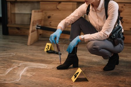 cropped view of female detective collecting evidence at crime scene