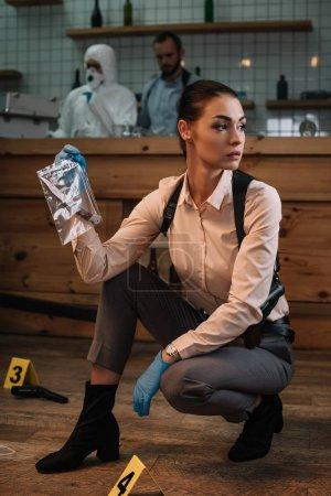 Photo pour Femme détective, recueillir des preuves sur les lieux du crime avec des collègues travaillant sur fond - image libre de droit