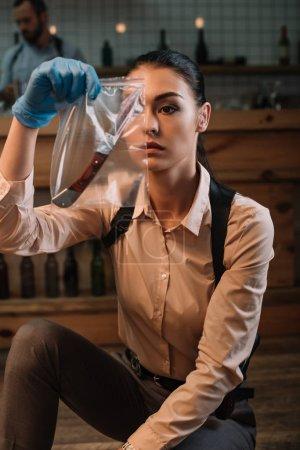 Foto de Centrada femenina detective mirando pruebas en la escena del crimen - Imagen libre de derechos