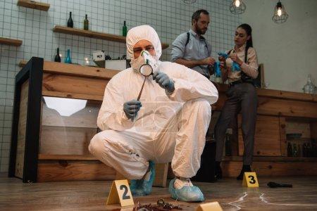 Photo pour Enquêteur médico-légal examinant des preuves avec loupe sur les lieux du crime avec des collègues travaillant derrière - image libre de droit