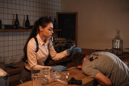 Foto de Concentarted mujer detective investigando el cadáver en la escena del crimen - Imagen libre de derechos