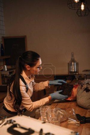 Foto de Vista lateral de la concentarted mujer detective examen cadáver en la escena del crimen - Imagen libre de derechos