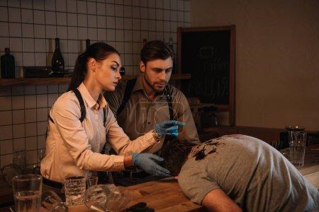 Photo pour Concentated mâles et femelles détectives recueillir des preuves de cadavre et enquêter sur les lieux du crime ensemble - image libre de droit