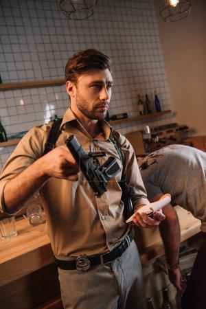 Foto de Hombre holding detective arma como evidencia en la escena del crimen - Imagen libre de derechos