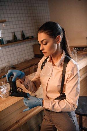 serious female detective in gloves investigating gun at crime scene