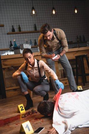 Photo pour Concentré de détectives féminins et masculins, enquête sur le cadavre à la scène du crime - image libre de droit