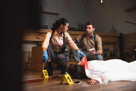 Photo pour Graves détectives féminins et masculins, enquête sur le cadavre au lieu du crime avec des marqueurs de la preuve - image libre de droit