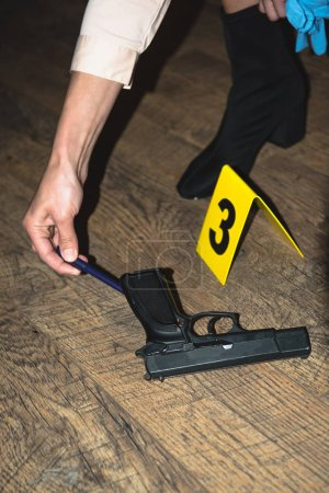 cropped view of hand examining gun near evidence marker at crime scene
