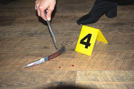 cropped view of hand examining evidence at crime scene