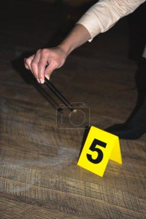 Foto de Recortar vista de mano examinar evidencias en la escena del crimen - Imagen libre de derechos