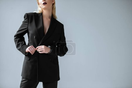 Photo for Cropped view of stylish girl posing in black suit isolated on grey - Royalty Free Image