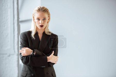 Photo pour Belle femme à la mode en costume noir posant sur fond gris - image libre de droit