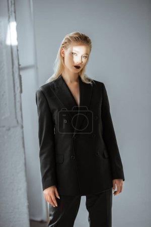 Photo pour Élégant modèle posant dans des tenues avec le faisceau de lumière sur le visage sur fond gris - image libre de droit