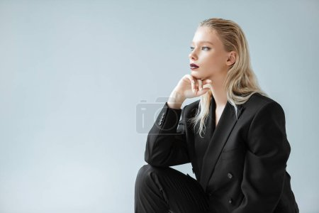 Photo for Attractive stylish girl posing in black suit for fashion shoot isolated on grey - Royalty Free Image