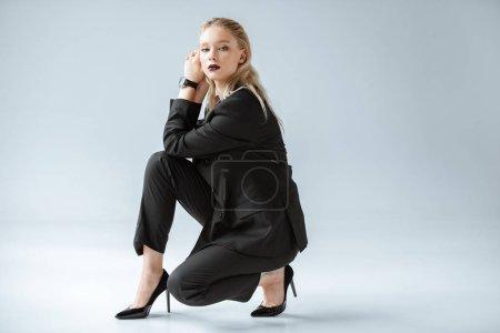 elegant young woman posing in trendy black suit on grey