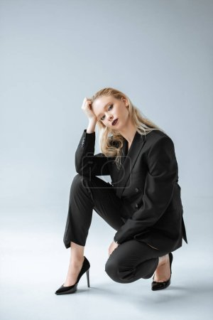 fashionable blonde model posing in trendy black suit on grey