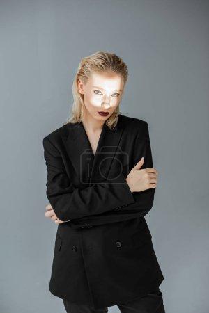 Photo pour Modèle attrayant en tenues avec un faisceau lumineux sur le visage isolé sur fond gris - image libre de droit