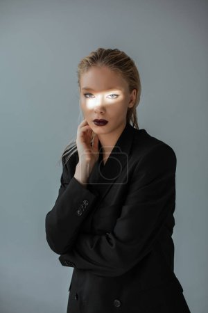 Photo pour Jeune fille à la mode, posant dans des tenues avec le faisceau de lumière sur le visage isolé sur fond gris - image libre de droit