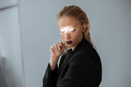 Photo pour Beau modèle posant dans des tenues avec le faisceau de lumière sur le visage sur fond gris - image libre de droit