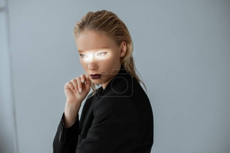 Photo for Attractive girl posing in formal wear with light beam on face isolated on grey - Royalty Free Image