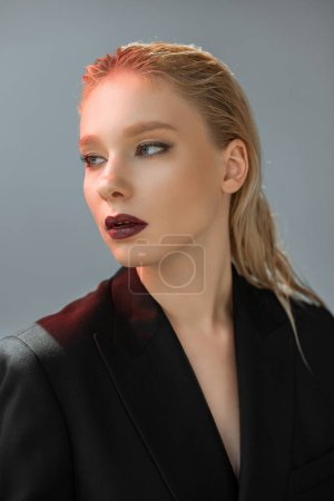 attractive stylish woman posing in black suit with red light isolated on grey