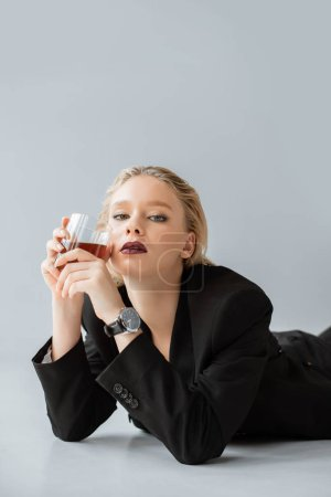 blonde stylish woman in black trendy suit holding glass of whiskey and lying on grey