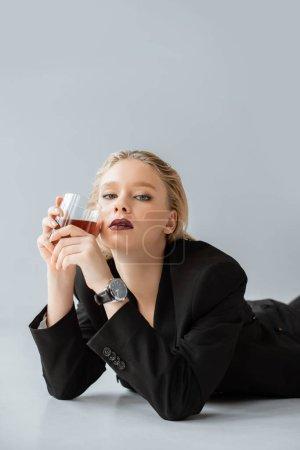 Photo pour Blonde femme élégante en costume tendance noir tenant le verre de whisky et de mentir sur fond gris - image libre de droit