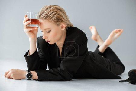 Foto de Atractiva mujer rubia en traje de moda negro sosteniendo la Copa de coñac y la mentira en gris - Imagen libre de derechos