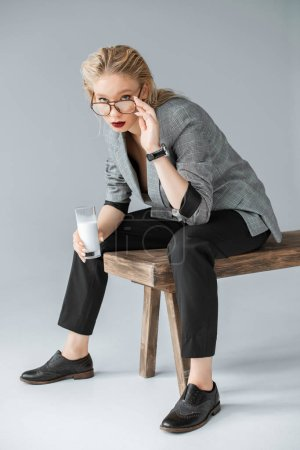 fashionable girl in eyeglasses holding glass of milk and sitting on wooden bench on grey