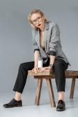"""Постер, картина, фотообои """"красивые модные женщина, сидящая на деревянной скамейке с стакан молока на серый"""""""