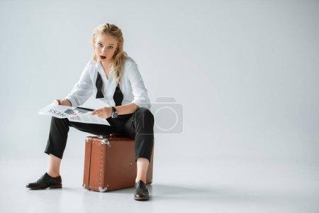 beautiful stylish girl reading business newspaper while sitting on vintage suitcase on grey