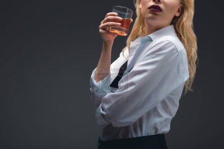 Photo pour Vue recadrée de la jeune fille en tenue formelle tenant verre de cognac, isolé sur gris foncé - image libre de droit