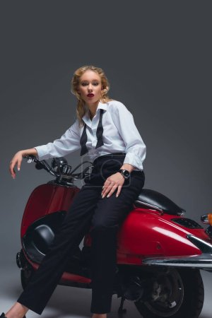 beautiful fashionable model posing on red retro scooter on grey