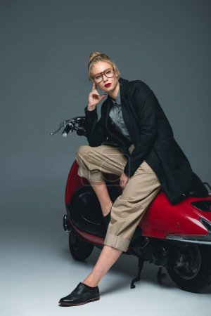 attractive fashionable young woman posing on red scooter on grey