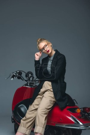 beautiful fashionable girl posing on red scooter isolated on grey
