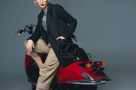 cropped view of fashionable girl posing on red scooter isolated on grey
